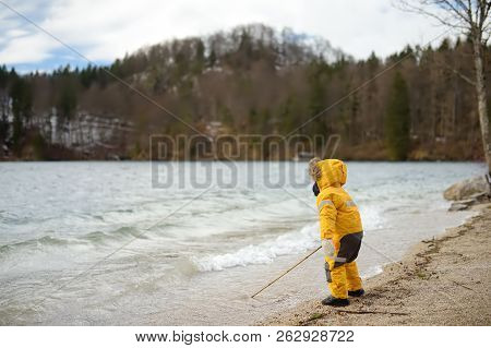 Little Boy Playing By Alpsee Lake, Located Near Hohenschwangau And Neuschwanstein Castles. Bavaria,