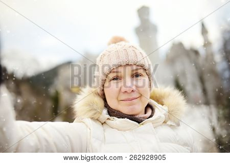 Mature Woman Making A Self Portrait (selfie) With Famous Royal Castle Neuschwanstein On Background.