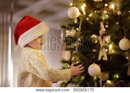 Little Boy Wearing Santa Hat Ready For Celebrate Christmas. Cute Child Decorating The Christmas Tree