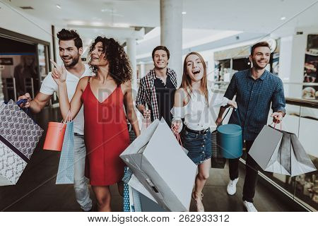 Company Of Friends Shopping In Mall With Packages. Shopping Concept. Girl In Red Dress. Woman In Whi