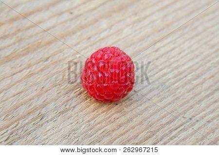 Single Raspberry On Wood