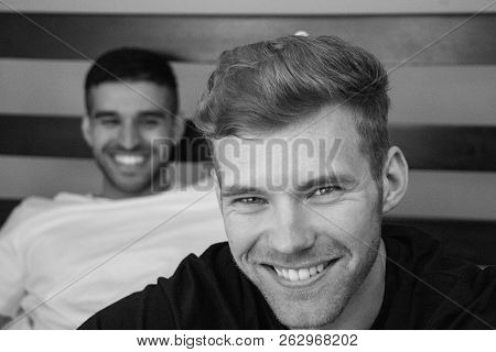 Gay Lovers Sitting In Bed With One Close To Camera And The Other Looking On. Both Are Smiling.