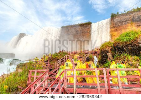 Niagara Falls, Usa - Aug 26, 2012: Poncho Clad Tourists Walk On The Wooden Stairs Leading To The Bri