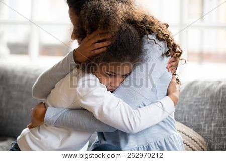 Black Mother And Daughter Embracing Sitting On Couch