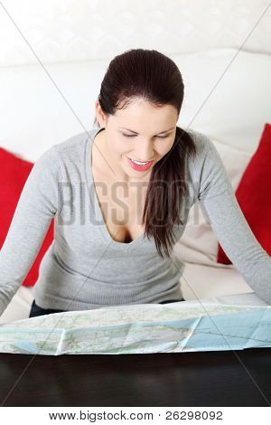 Front view portrait of a young beautiful woman, sitting on a couch at home and having a look at a map.