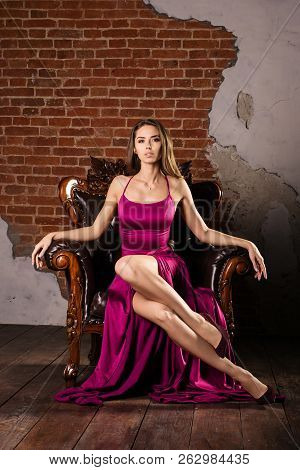 Magnificent Young Woman In Luxurious Dress A Is Sitting In A Chair In A Luxury Apartment. Classic Vi