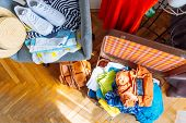 overloaded valise with clothes. prepared garment on chair. travel concept poster