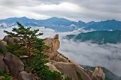 Hanging stone at the Ulsanbawi Rock against the fog seorak mountains at the Seoraksan National Park, South korea poster