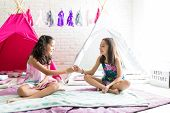 Happy friends taking pinky promises while sitting on duvets against tipi tents at home poster