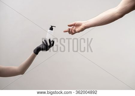 Hand With Dispenser Of Sterilizer Transfers To Another Female Hand