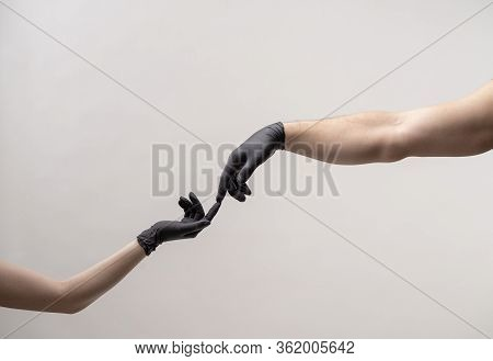 Hands In Black Silicone Gloves Stretches To Each Other To Touch