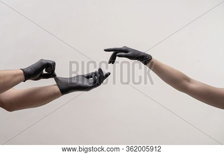 Male And Female Hand In Black Gloves Stretch To Touch Each Other.