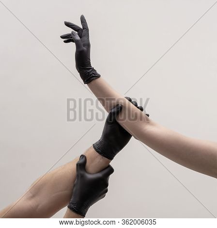 Male And Female Hand In Black Gloves. Hold Each Other.