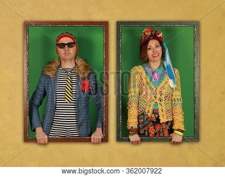 Couple Of Freaks Hold Picture Frames And  Look At The Camera On A Yellow Background. Crazy People Po