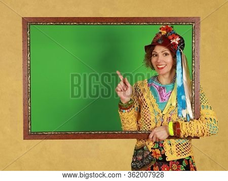 Middle Aged Female Freak Holds A Picture Frame In A Studio On A Yellow Background