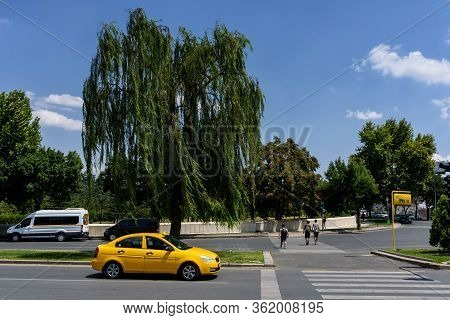 Ankara, Turkey - June 24, 2018: Yellow Taxi Stands Near A Beautiful Spreading Tree Near The Entrance
