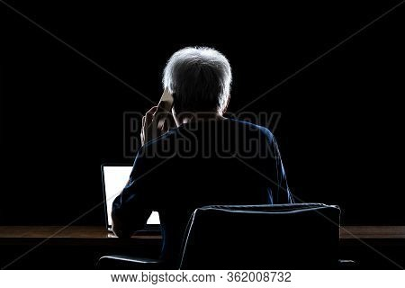 Back View Of A Man With Gray Hair Working From Home Late At Night Talking On His Phone While Using H