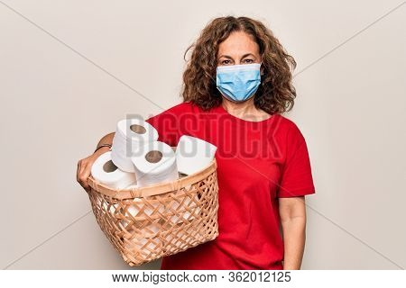 Middle age woman wearing coronavirus protection mask holding big amount of toilet paper for hysteria looking positive and happy standing and smiling with a confident smile showing teeth
