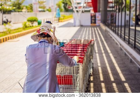 Female Employee Collects Shopping Trolleys Outside A Branch Of Supermarket Chain