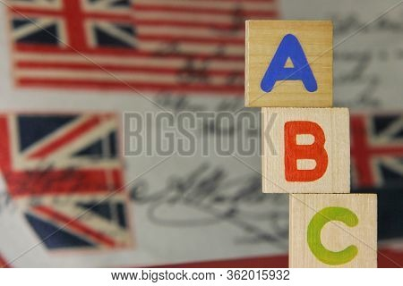 Abc-letters Of The English Alphabet On Wooden Cubes On The Background Of Images Of The English Flag.