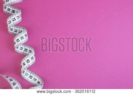 Unfolded White Tape Measure, White Measuring Tape Isolated On Pink Background. Close The Tailor Meas