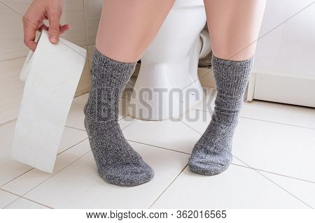 Woman Legs In Socks On A Toilet With A Roll Of Toilet Paper In Hands, Digestive Problems And Defecat