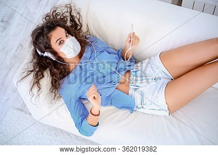 Coronavirus concept. Staying at home and social distancing. A young girl in a medical mask stays at home, listens to music, relaxes and communicates with friends through social networks.