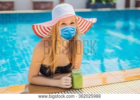 Woman In Medical Mask With A Green Smoothies Of Spinach And Banana On The Background Of The Pool. He