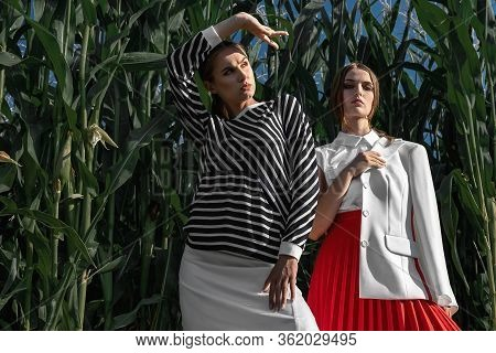 Portrait Of Two Fair-haired Girls In Fashionable And Stylish Clothes, Among The Foliage Of A Corn Fi