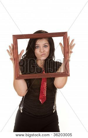 A teen girl holding up a picture frame making a silly face while she is wearing a red tie and suspenders. poster