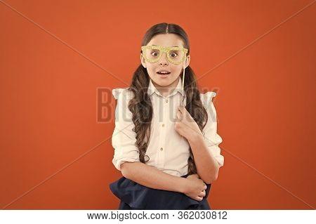School Party Concept. What Does It Mean Being Smart. Little Smart Schoolgirl On Orange Background. C