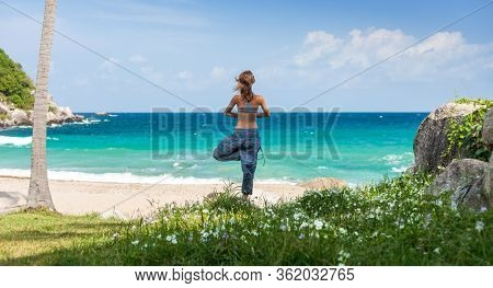 Young woman performs yoga exercises on a green lawn with sea on the background