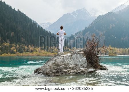 A Man Stands On A Stone In The Center Of A Mountain Lake And Practices Yoga. Pose Vrikshasana.