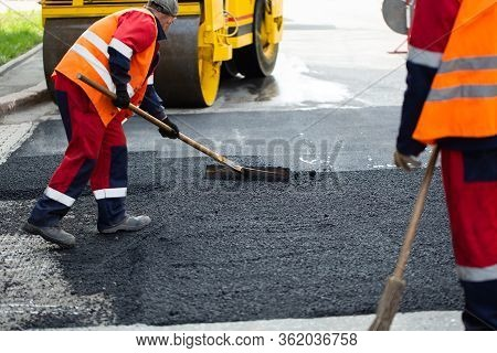 The Road Workers' Working Group Updates Part Of The Road With Fresh Hot Asphalt And Smoothes It For