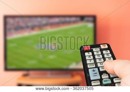 Caucasian Man Watching American Football Game On Tv At Home. Changing Channels And Adjusting Volume