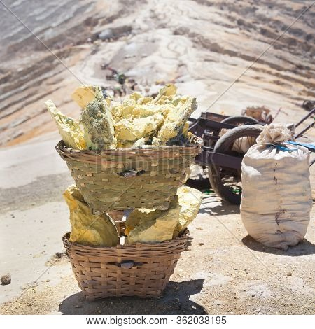 Heavy Basket Laden By Pieces Of Natural Sulfur To Carry By Miners From Crater Mine. Manual Labour In
