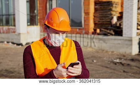 Male Construction Worker In Overalls And Medical Mask Flipping Through News About Coronavirus In Mob