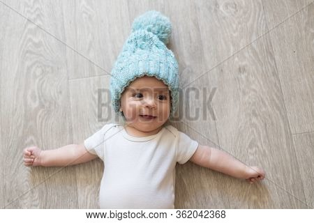 Newborn Baby. A Little Boy In White Clothes And Blue Winter Hat. Beautiful Portrait Of A Toddler. Bi