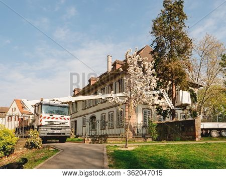 Selestat, France - Apr 15, 2019: Iveco Truck With Power Tower Lift Cutting A Tree In Front Of Beauti