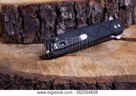 Folding Pocket Knife In The Folded Position. Folded Knife On A Wooden Surface. Clip And Cullet On Th