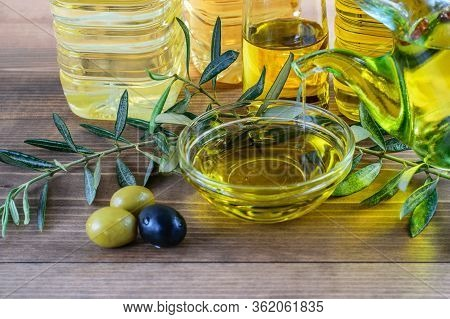 Assortment Of Olive Oil Bottles, Olive Oil Dripping In Glass Bowl, Some Olives And Olive Tree Branch