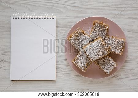 Homemade Tasty Applesauce Cake On A Pink Plate, Blank Notepad On A White Wooden Surface, Top View. F