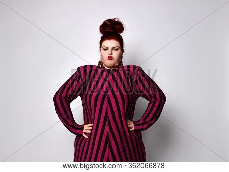 Fatty Ginger Girl With Bun Hairstyle, In Black And Purple Striped Dress And Earrings. She Has Put He