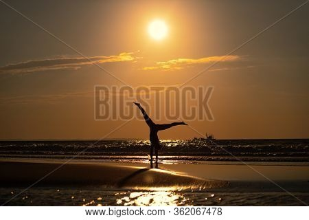 View of woman turning upside down on the beach in sunrise