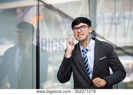 Young Businessman Running While Talking On The Mobile Phone During Rush Hour. Business Rushing Conce