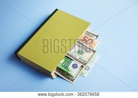 Concept of financial literacy and money management. Book with a bookmark in the form of a dollar and euro bill