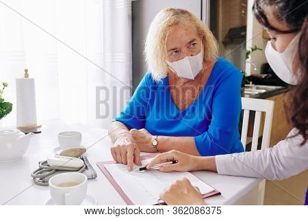 Doctor In Medical Mask Visiting Senior Patient At Home And Explaining Her Results Of Cardiogram