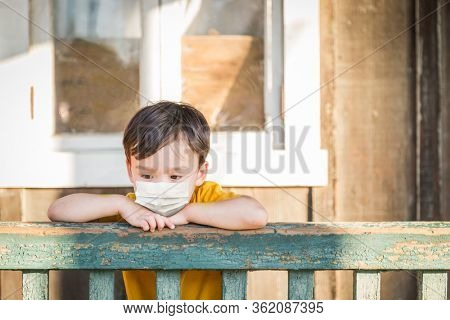 Young Mixed Race Chinese and Caucasian Boy Playing Alone Wearing Medical Face Mask Outside.