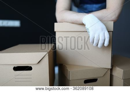 Gloved Hands Loader Lie On Cardboard Boxes Office. Relocation Service Packed Property In Separate Bo