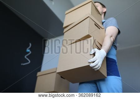 Loader Man Carries Cardboard Boxes In Office. Company Provides Freight Transport At Appointed Time,